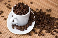 White cup with coffee beans on wicker placemat Stock Image