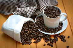 White cup with coffee beans on wood  background Royalty Free Stock Image