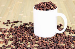 White cup with coffee beans is on a wooden table. tinted image. Horizontal Stock Image