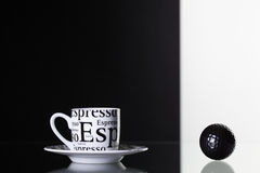 White cup of coffee and black golf ball Stock Images