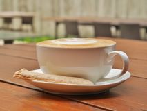 White cup of coffee with blur background of outdoor cafe. Stock Photography