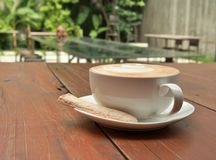White cup of coffee with blur background of outdoor cafe. Stock Photo