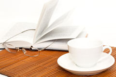 White cup of coffee and book with glasses Stock Photo