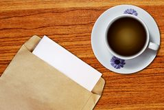 White cup of coffee and brown envelope Royalty Free Stock Photo