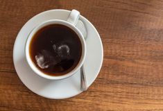 White cup with coffee on brown wooden table. Aerial view of a cup of hot coffee served on a brown color table with wood texture stock image