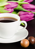 White cup of coffee with candies and purple tulips. White cup of coffee with chocolate candies and bunch of purple tulips on the dark background Stock Image