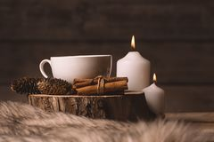 White cup with coffee, candles, cinnamon, fur and cones royalty free stock photo