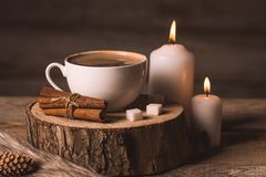 White cup with coffee, candles, sugar, cinnamon, pinecone and fur stock photo