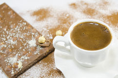 White cup of coffee and a chocolate in the background Royalty Free Stock Images