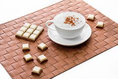 White cup of coffee with chocolate on brown Royalty Free Stock Images