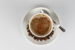 Cup of coffee with cocoa powder forming a heart on the foam. White cup of coffee with cocoa powder forming a heart on the foam, with some beans on the saucer royalty free stock photos