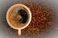 White cup of coffee on coffee bean background Royalty Free Stock Image