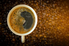 White cup of coffee on coffee bean background Stock Image
