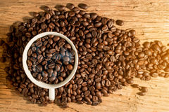 White cup of coffee and coffee bean on wood texture Stock Images