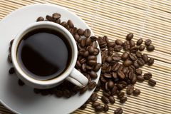 White cup of coffee and coffee beans stock photography