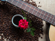 White cup of coffee, with coffee beans backgound and red rose, g