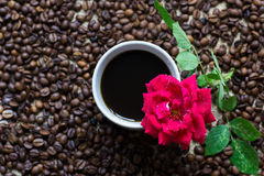 White cup of coffee, with coffee beans backgound and red rose Stock Image