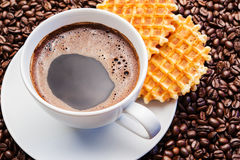 White cup of coffee on coffee beans with belgian waffles. White cup of coffee with roasted coffee beans Stock Photos