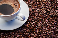 White cup of coffee on coffee beans. White cup of coffee with roasted coffee beans Royalty Free Stock Images