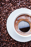 White cup of coffee on coffee beans. Top view. White cup of coffee with roasted coffee beans Stock Images