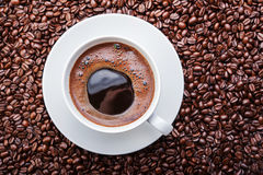 White cup of coffee on coffee beans. Top view. White cup of coffee with roasted coffee beans Stock Photo