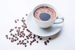 White cup of coffee with coffee beans on white table. White cup of coffee with roasted coffee beans Stock Image