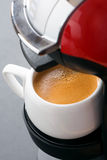 White cup of coffee in the coffee machine, vertical Royalty Free Stock Image