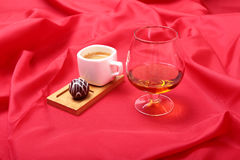 White cup of coffee and cognac in a glasses, pralines on red background. Stock Photos