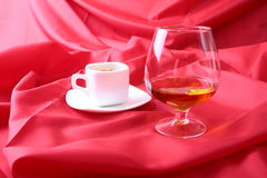 White cup of coffee and cognac in a glasses, pralines on red background. Stock Photo