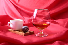White cup of coffee and cognac in a glasses, pralines on red background. Stock Photography