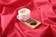 White cup of coffee and cognac in a glasses, pralines on red background. Royalty Free Stock Photos