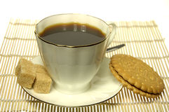 White Cup of coffee with cookie and sugar. Over yellow mat Stock Image
