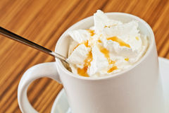 White cup of coffee with cream and caramel Royalty Free Stock Photography