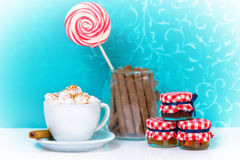 White cup of coffee with cream, cookies and lollipop. Stock Photography