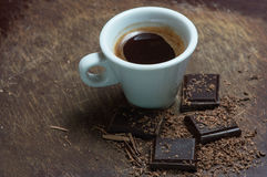 White cup of coffee and dark chocolate. Background Stock Images