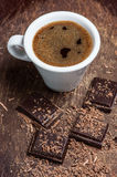 White cup of coffee and dark chocolate. Background Stock Photo