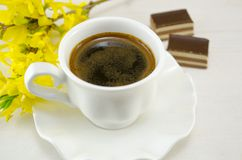 White cup of coffee with dessert on a table decorated with flowe Royalty Free Stock Image