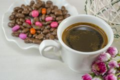 White cup of coffee with dessert on a table decorated with flowe Royalty Free Stock Images