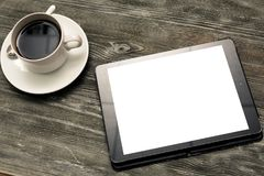White cup of coffee with digital tablet on table Royalty Free Stock Photos