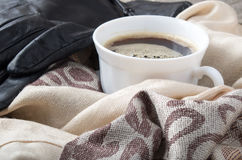 White cup of coffee in the folds of the female scarf Stock Photos
