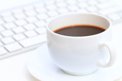 White cup of coffee in front of computer keyboard Royalty Free Stock Photo