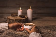 White cup with coffee in the hands of a girl, fur, cones and candles royalty free stock photo