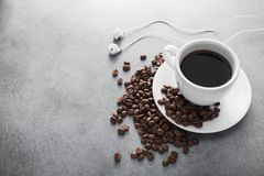 White cup of coffee with headphone and coffee beans Royalty Free Stock Image