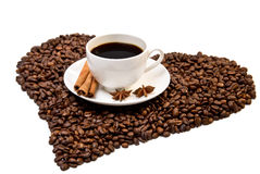 White cup of coffee on heart shaped coffee beans Royalty Free Stock Image