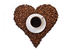 White cup of coffee on heart shaped coffee beans Royalty Free Stock Photography