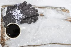 A white Cup of coffee and knitted gray gloves with a pattern on a wooden bench in the snow during a snowfall. Cozy winter card. royalty free stock photography