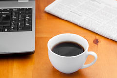 White cup of coffee with laptop and newspaper Stock Image