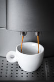 White cup in coffee machine, espresso preparing Royalty Free Stock Photo