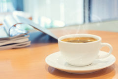White cup of coffee with magazine on wood table. royalty free stock images