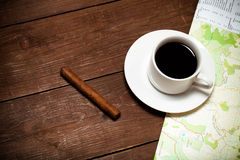 White cup of coffee, map and cigar on old wooden table. Toned.  royalty free stock images